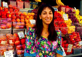 Behind Emily is a stand containing fruits from Central Asia. Her research aims in part to untangle the myriad ways both the fruits and the people selling them come to Saint Petersburg.